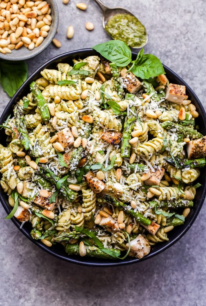 Grilled Chicken and Asparagus Pesto Pasta in black bowl with pine nuts on the side and a spoon with pesto on it.