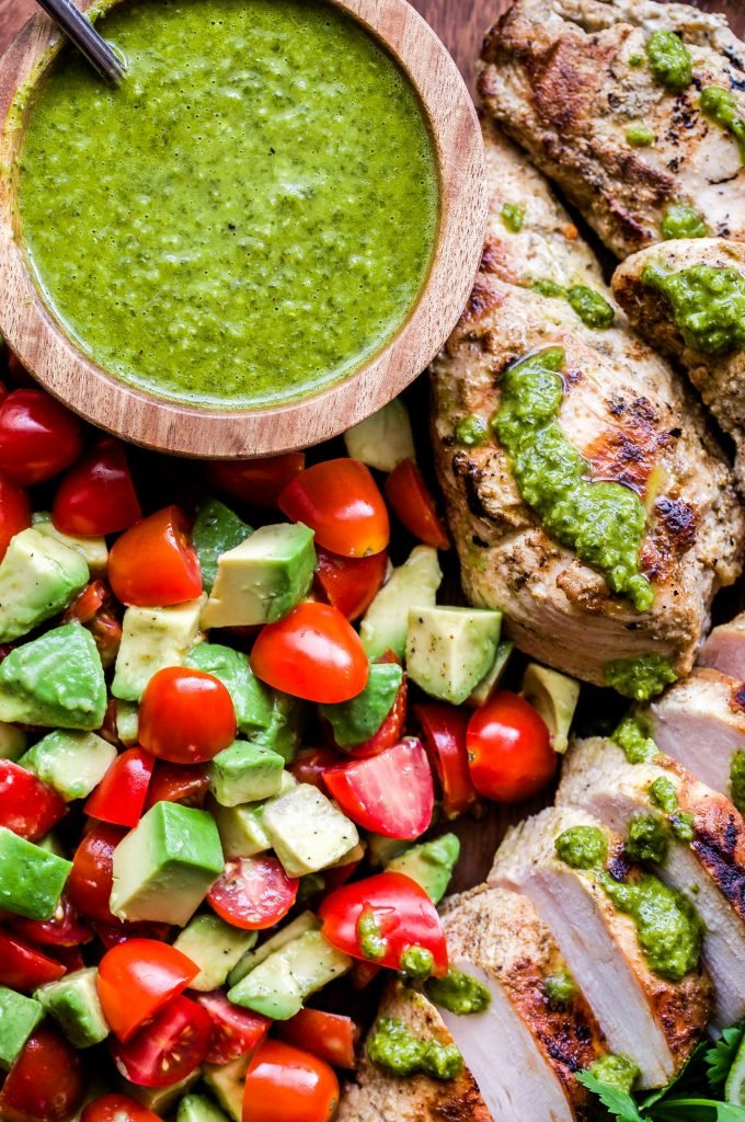 Grilled Chicken with Tomato Avocado Salad drizzled with green chimichurri sauce. Overhead, closeup photo.