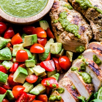Grilled Chicken with Tomato Avocado Salad drizzled with green chimichurri sauce