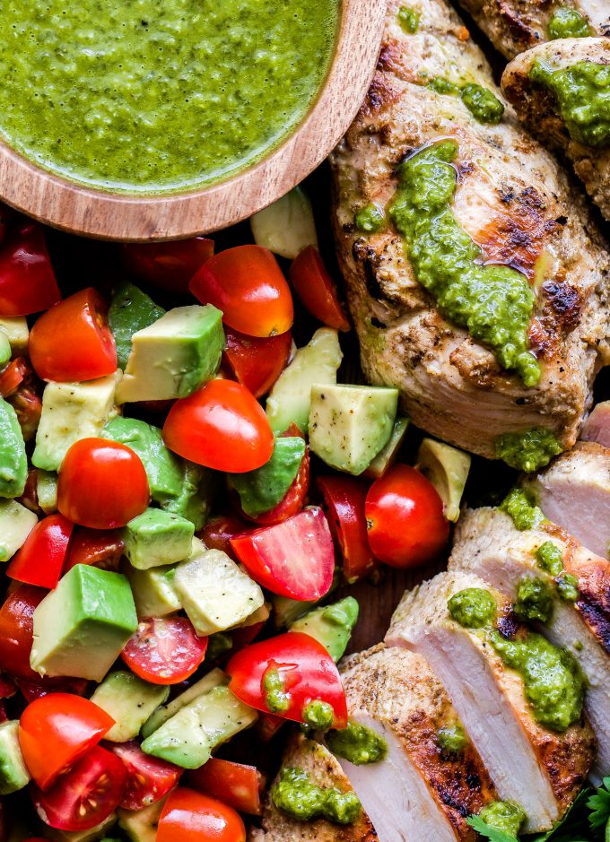 Grilled Chicken with Tomato Avocado Salad with chimichurri in a small wooden bowl