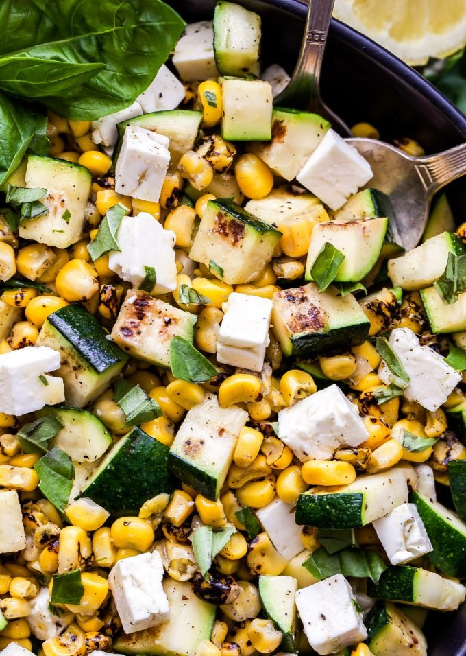 Grilled Zucchini Corn Salad with Lemon Basil Vinaigrette with serving spoons in the salad