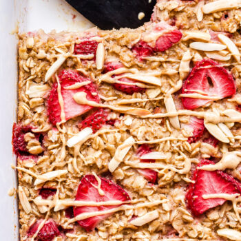 overhead photo of Strawberry Vanilla Baked Oatmeal in white dish with slice cut out.