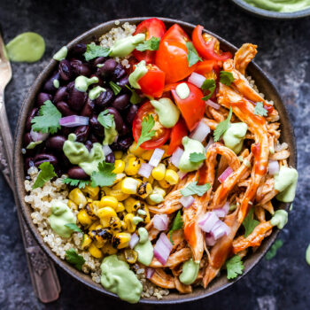 Barbecue Chicken Quinoa Bowls topped with black beans, tomatoes, corn and avocado crema.