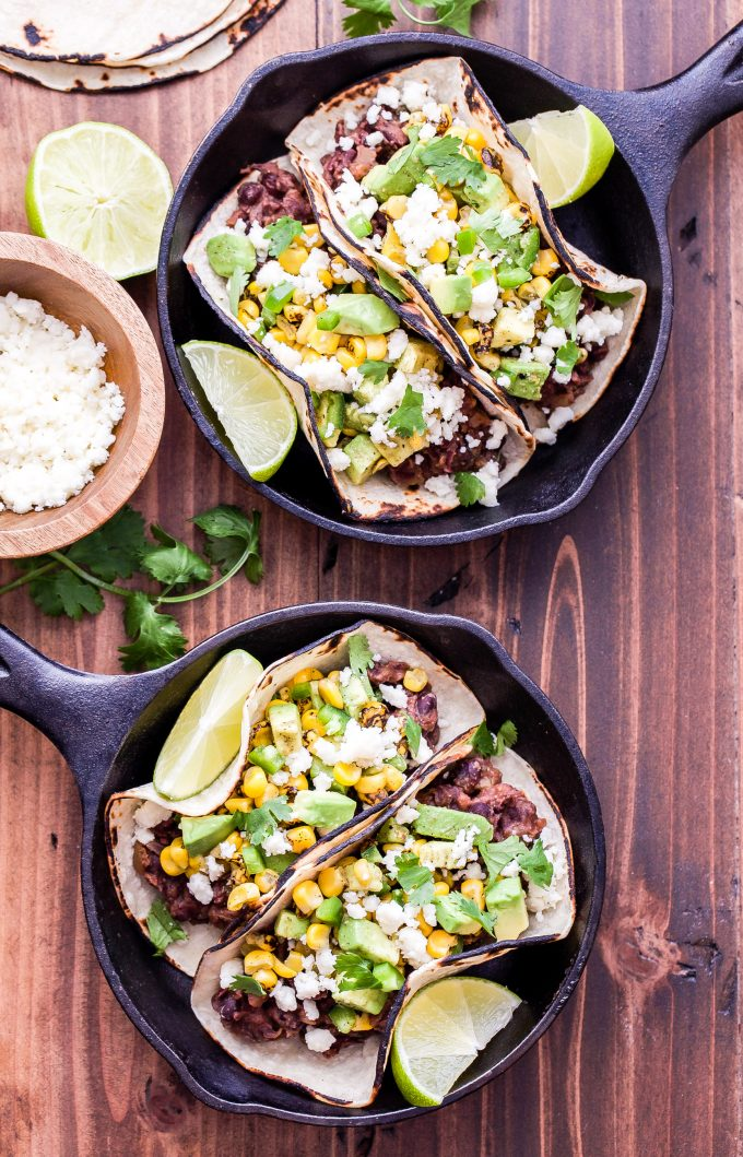 2 cast iron skillets with Black Bean Tacos with Avocado Corn Salsa in them and a small wooden bowl of queso fresco on the side.
