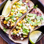 Two Black Bean Tacos with Avocado Corn Salsa overhead photo in cast iron skillet with lime wedges.