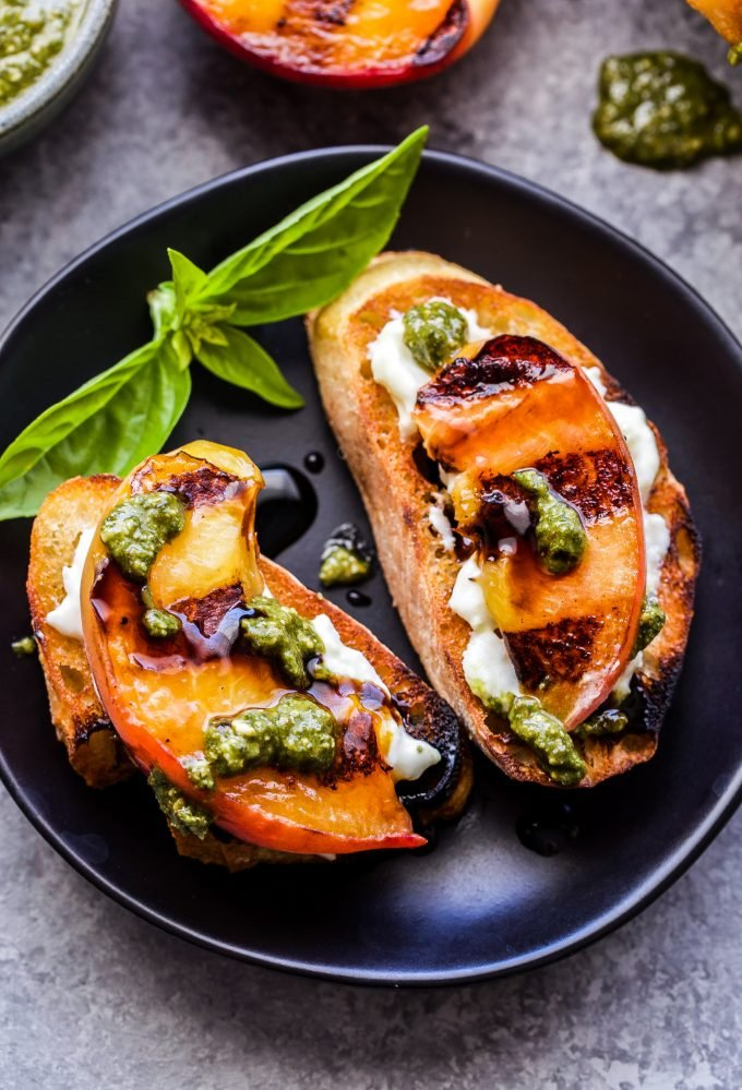 Assembled Grilled Peach and Burrata Crostini. Baguette slice topped with burrata, a peach slice and drizzled with pesto and balsamic glaze.