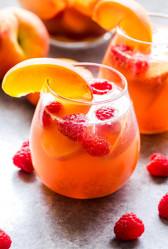 Peach Rosé Sangria in stemless glass garnished with a peach slice and fresh raspberries.