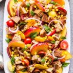 Peach, Tomato and Corn Panzanella on a white serving plate with spoons on the side of the plate.
