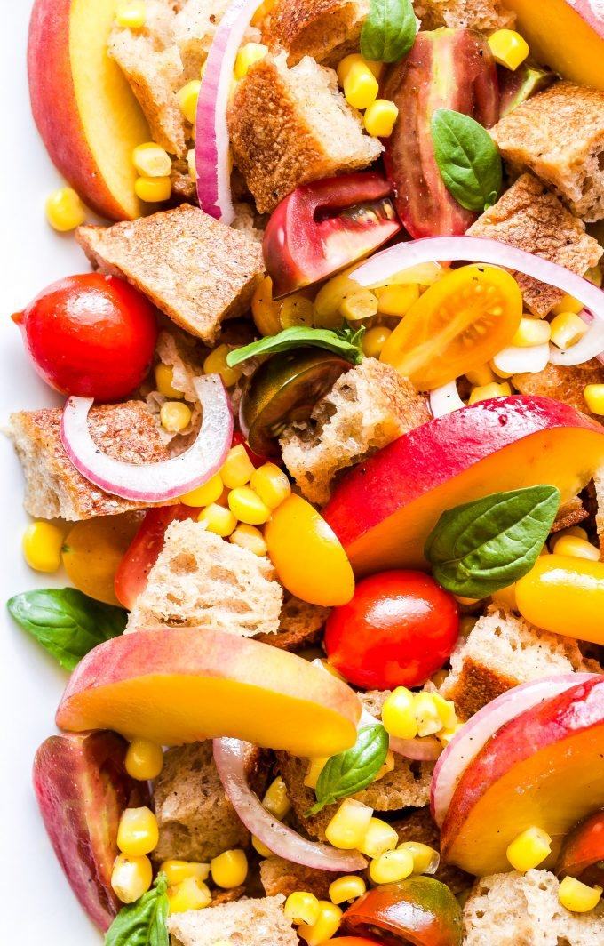 Peach, Tomato and Corn Panzanella on white serving plate