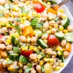 Summer Quinoa Salad in white bowl with spoon. Salad has chickpeas, corn, tomatoes, cucumbers and basil