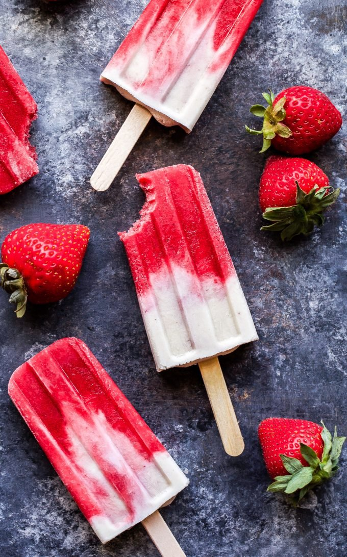 Three Vegan Strawberries and Cream Popsicles with fresh strawberries scattered next to them.