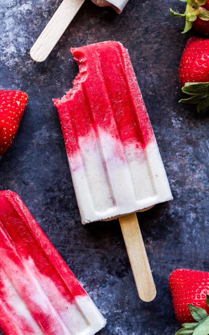 Vegan Strawberries and Cream Popsicle with bite taken out of it.