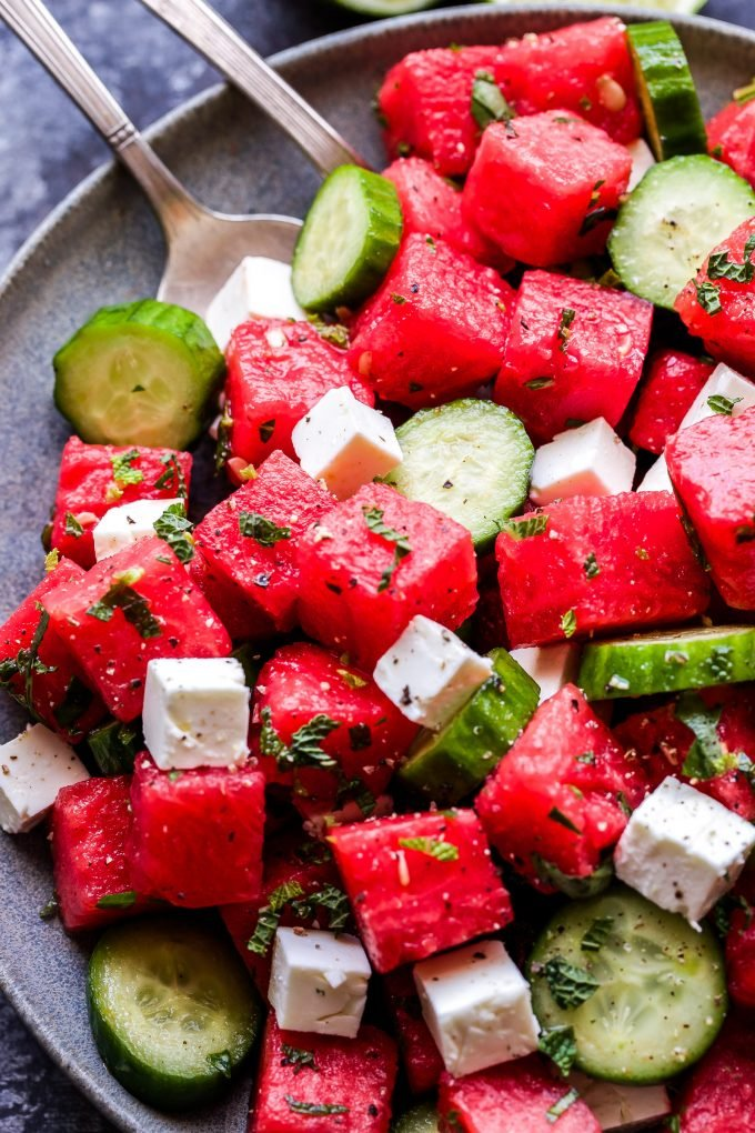 Watermelon Salad with Cucumber and Feta on grey plate with serving spoons
