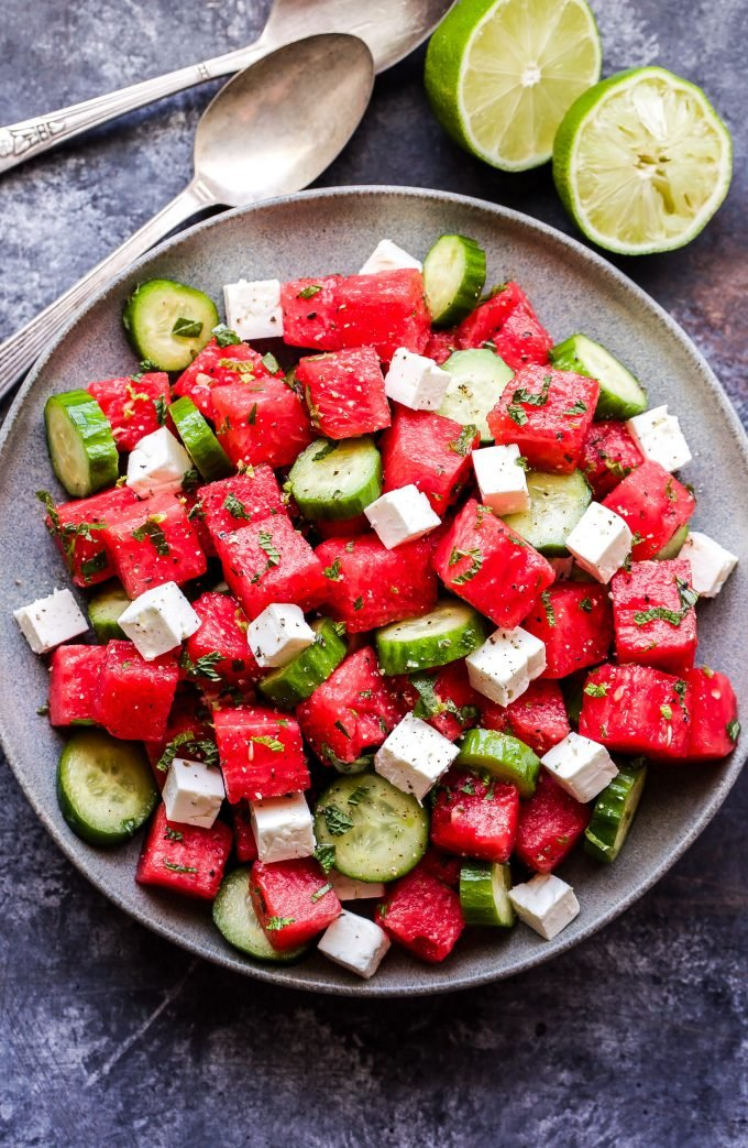 Watermelon Salad with Cucumber and Feta overhead photo of salad on grey plate with serving spoons and halved lime on the side