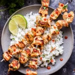 Overhead photo of Coconut Lime Chicken Skewers over rice with lime wedges on gray plate.