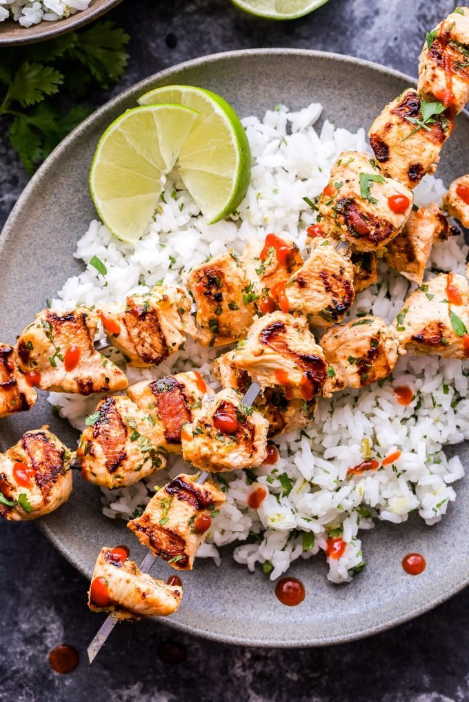Coconut Lime Chicken Skewers over rice with lime wedges on gray plate.