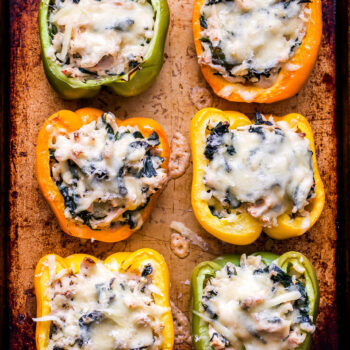 Overhead photo of six Creamy Chicken, Spinach and Rice Stuffed Pepper halves on a sheet pan.