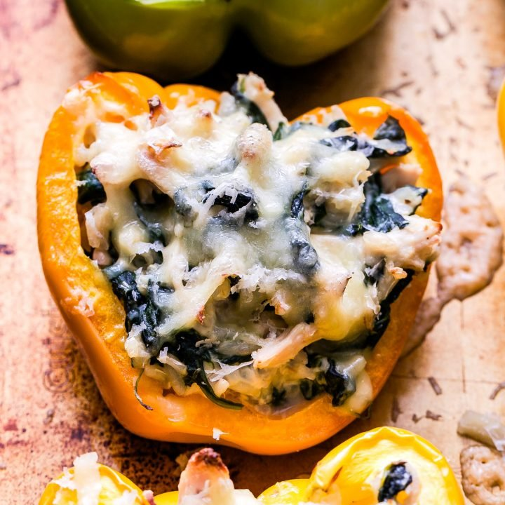 An orange Creamy Chicken, Spinach and Rice Stuffed Pepper topped with melted mozzarella cheese.