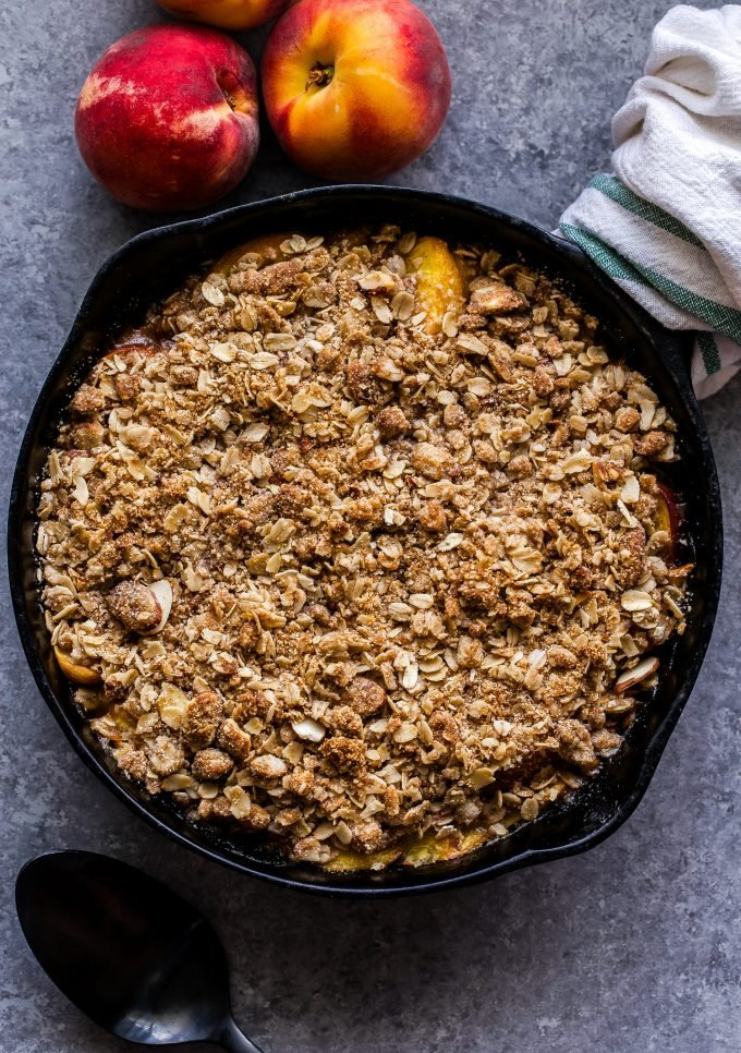 Gluten Free Peach Crisp in black cast iron skillet with dish towel around the handle.