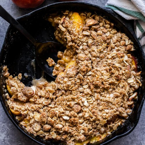 Gluten Free Peach Crisp in black cast iron skillet with a scoop of the crisp taken out and dish towel around the handle.