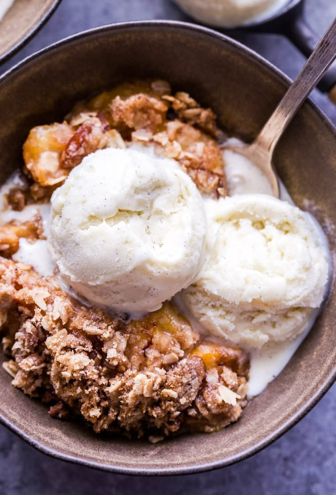 Gluten Free Peach Crisp in bowl with two scoops of vanilla ice cream.