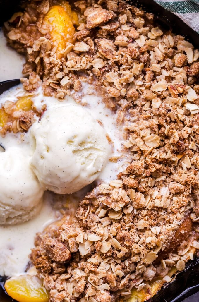 Gluten Free Peach Crisp in cast iron skillet topped with melting scoops of vanilla ice cream.