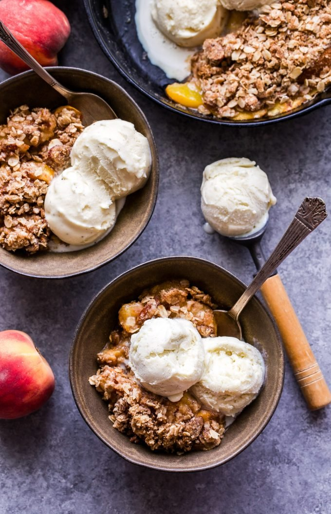 Gluten Free Peach Crisp in two bowls topped with scoops of vanilla ice cream.