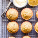 Overhead photo of Lemon Zucchini Muffins on wire cooling rack with gray bowl full of honey butter and a butter knife.