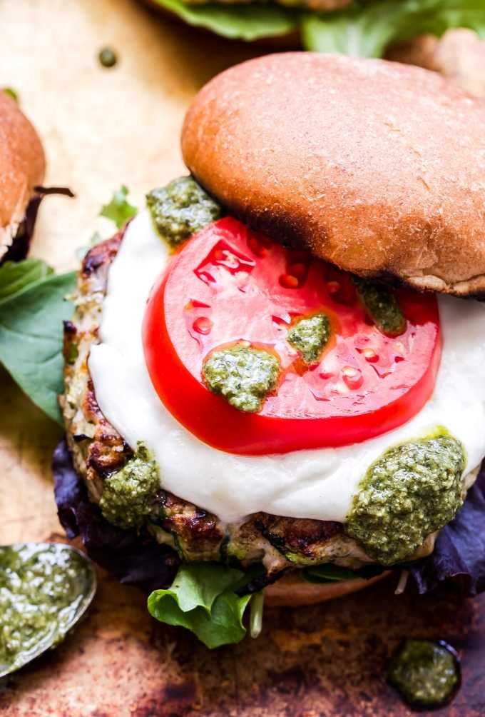 Pesto Zucchini Turkey Burger on a bun topped with mozzarella cheese, tomato slice and pesto.