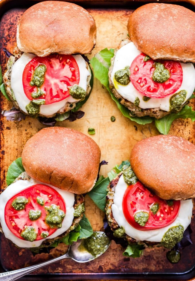 Four Pesto Zucchini Turkey Burgers on sheet pan with spoon of pesto.