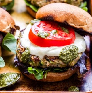 Pesto Zucchini Turkey Burger topped with fresh mozzarella a tomato and pesto