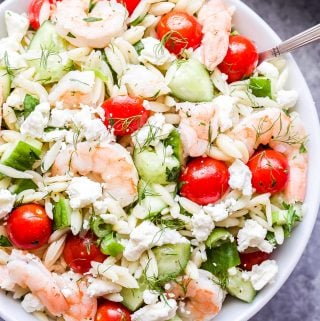 Shrimp Orzo Salad with Feta and Herbs with spoons in white serving bowl.