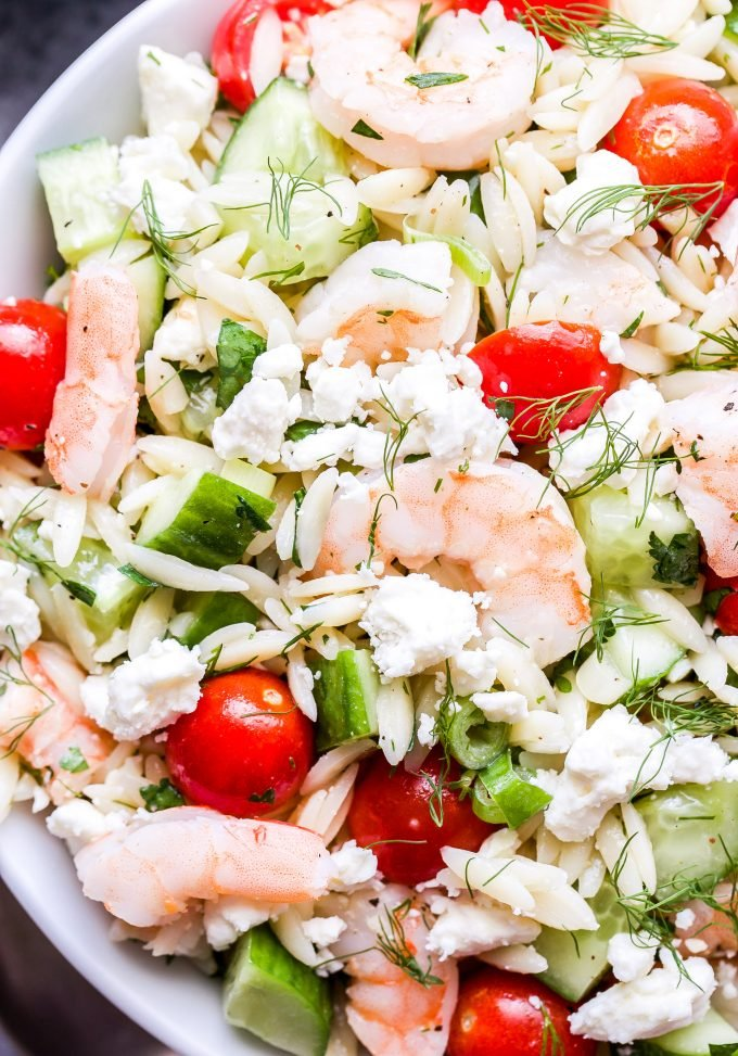 Closeup photo of Shrimp Orzo Salad with Feta and Herbs in white bowl.