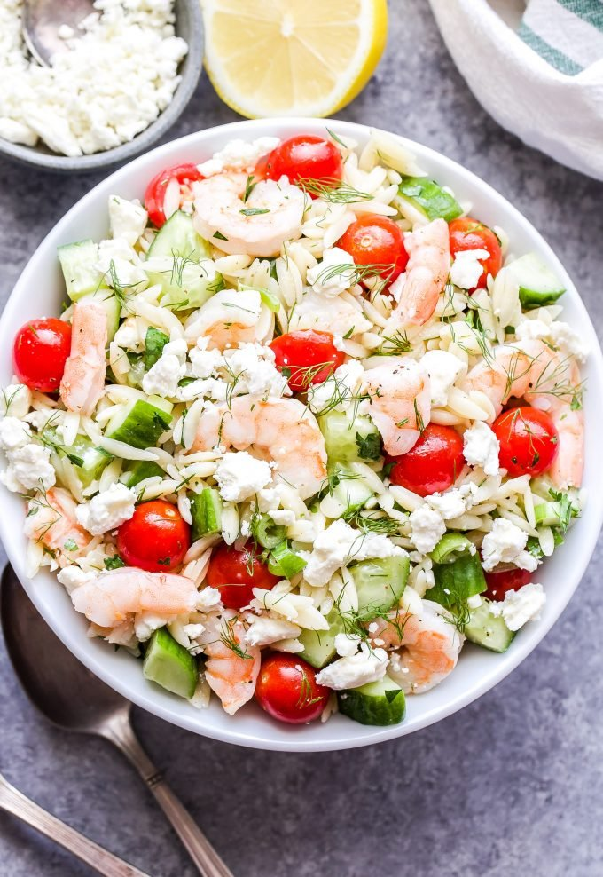 Shrimp Orzo Salad with Feta and Herbs in white bowl with feta and lemon half on the side.