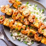 Teriyaki Shrimp and Pineapple Skewers on gray plate with quinoa, garnished with green onions and sesame seeds.