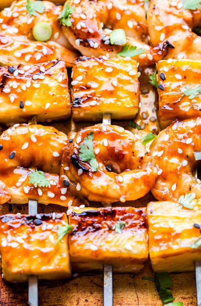 Close up of Teriyaki Shrimp and Pineapple Skewers garnished with sesame seeds and cilantro