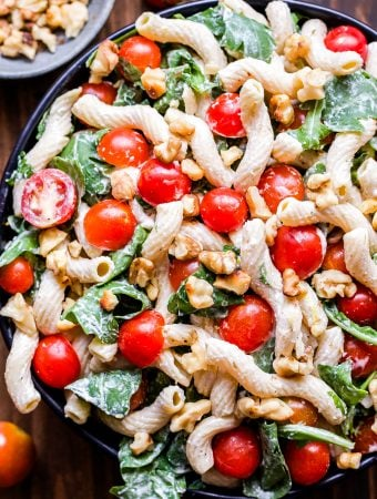 Tomato, Arugula and Goat Cheese Pasta in bowl topped with walnuts.