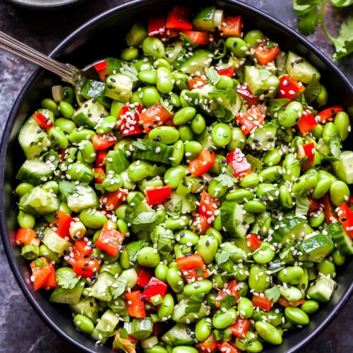 Asian Edamame Salad in black serving bowl with spoon in bowl and bowl of vinaigrette on the side.