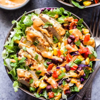 Fiesta Ranch Salad topped with Salsa Verde Chicken slices in a bowl with a side of taco spiced ranch dressing on the side.