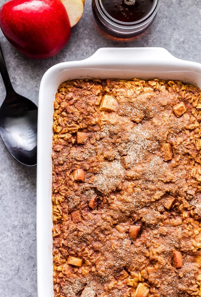 Overhead photo of Pumpkin Apple Baked Oatmeal topped with cinnamon sugar in a white baking dish