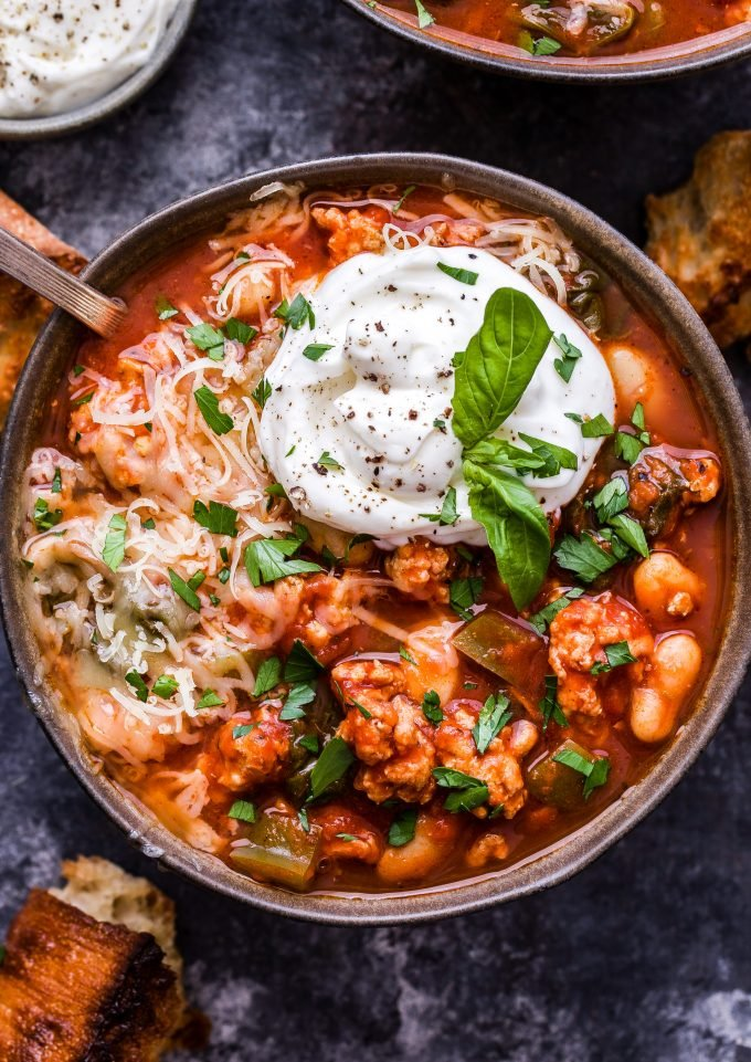 Slow Cooker Italian Turkey Chili in bowl with spoon topped with a dollop of ricotta and garnished with basil leaves.