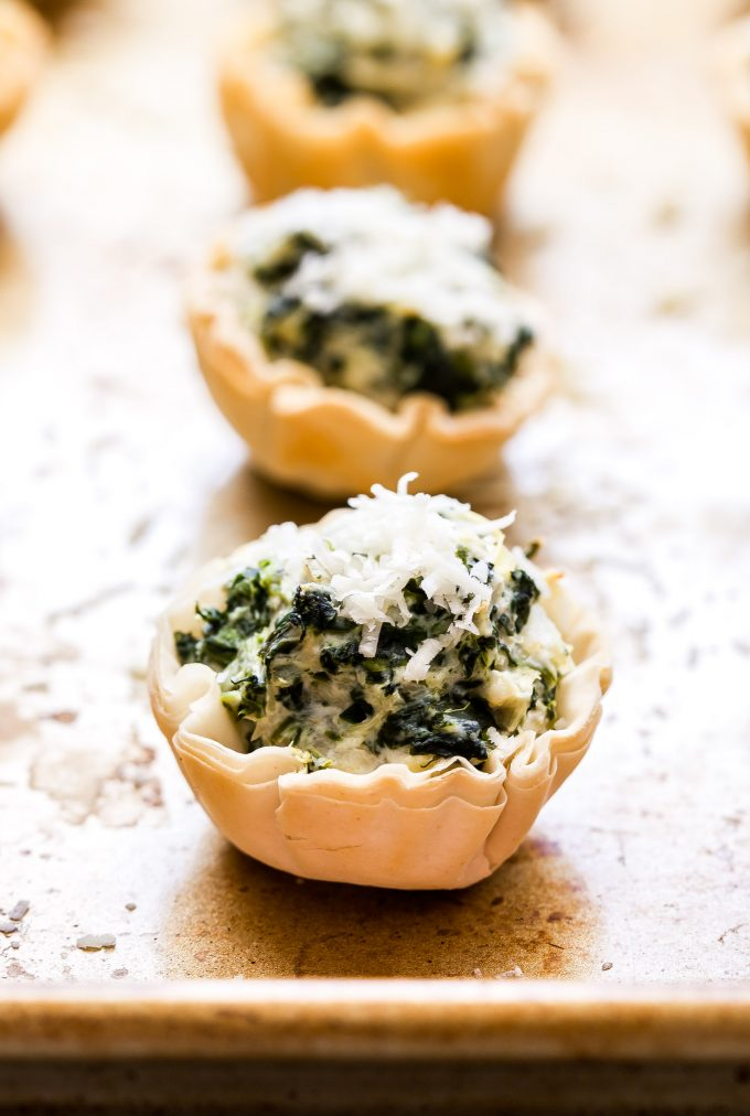 Spinach Artichoke Dip in mini phyllo shells topped with parmesan cheese.