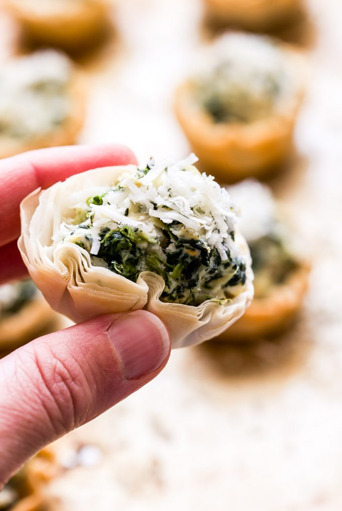 Hand holding a Spinach Artichoke Dip filled mini Phyllo shell.