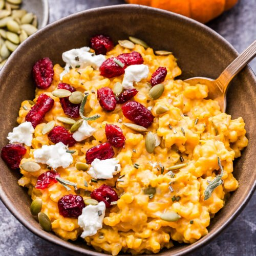 Bowl of Baked Pumpkin Goat Cheese Risotto topped with dried cranberries, pepitas and goat cheese crumbles.