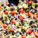Green Chile Chicken Enchilada Quinoa Casserole topped with tomatoes, avocado, cheese, red onions.