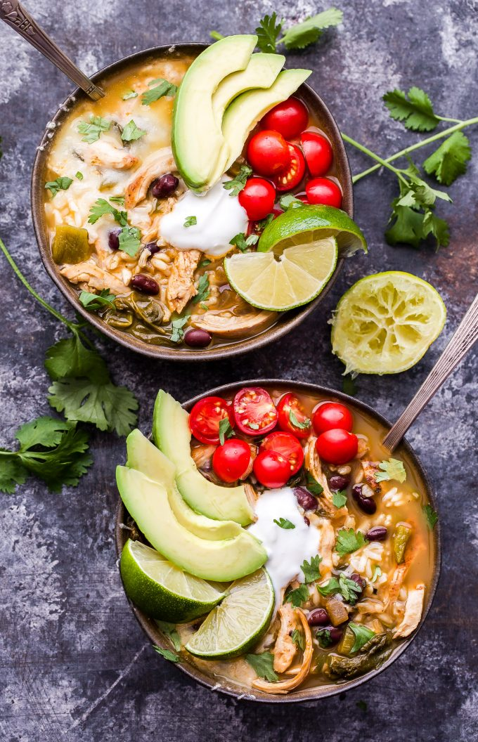 Two bowls of Southwest Chicken and Rice Soup topped with avocado, tomatoes, lime wedges, sour cream and cilantro.