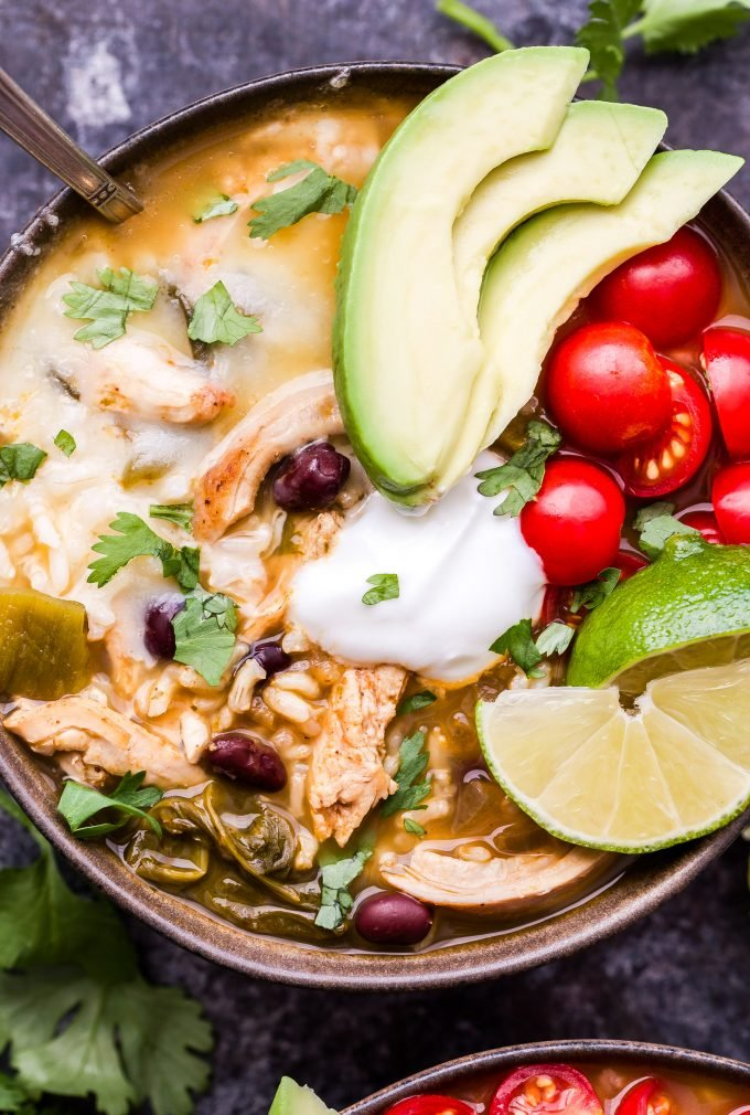 Closeup photo of Southwest Chicken and Rice Soup in bowl with a spoon topped with avocado, tomatoes, lime wedges, sour cream and cilantro.