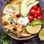Overhead photo of Southwest Chicken and Rice Soup in bowl with a spoon topped with avocado, tomatoes, lime wedges, sour cream and cilantro.