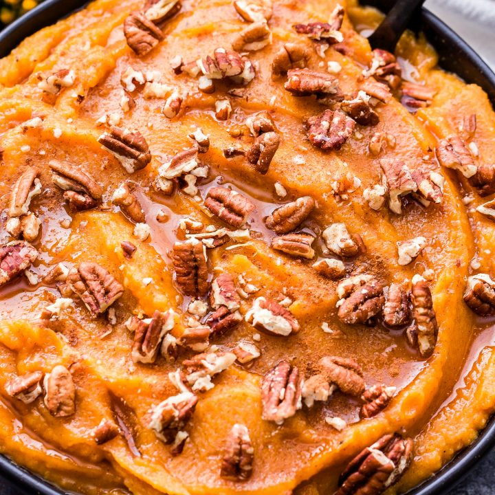 Cinnamon Maple Mashed Sweet Potatoes and Butternut Squash topped with chopped pecans in a black bowl with a black spoon in the bowl.