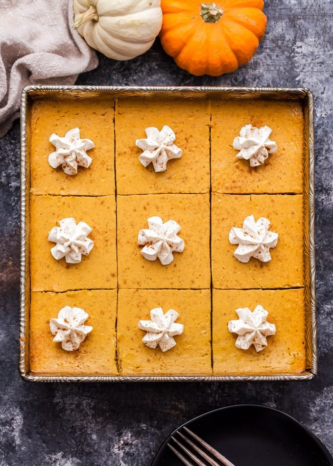 Creamy Pumpkin Pie Bars in square metal baking pans topped with whipped cream.